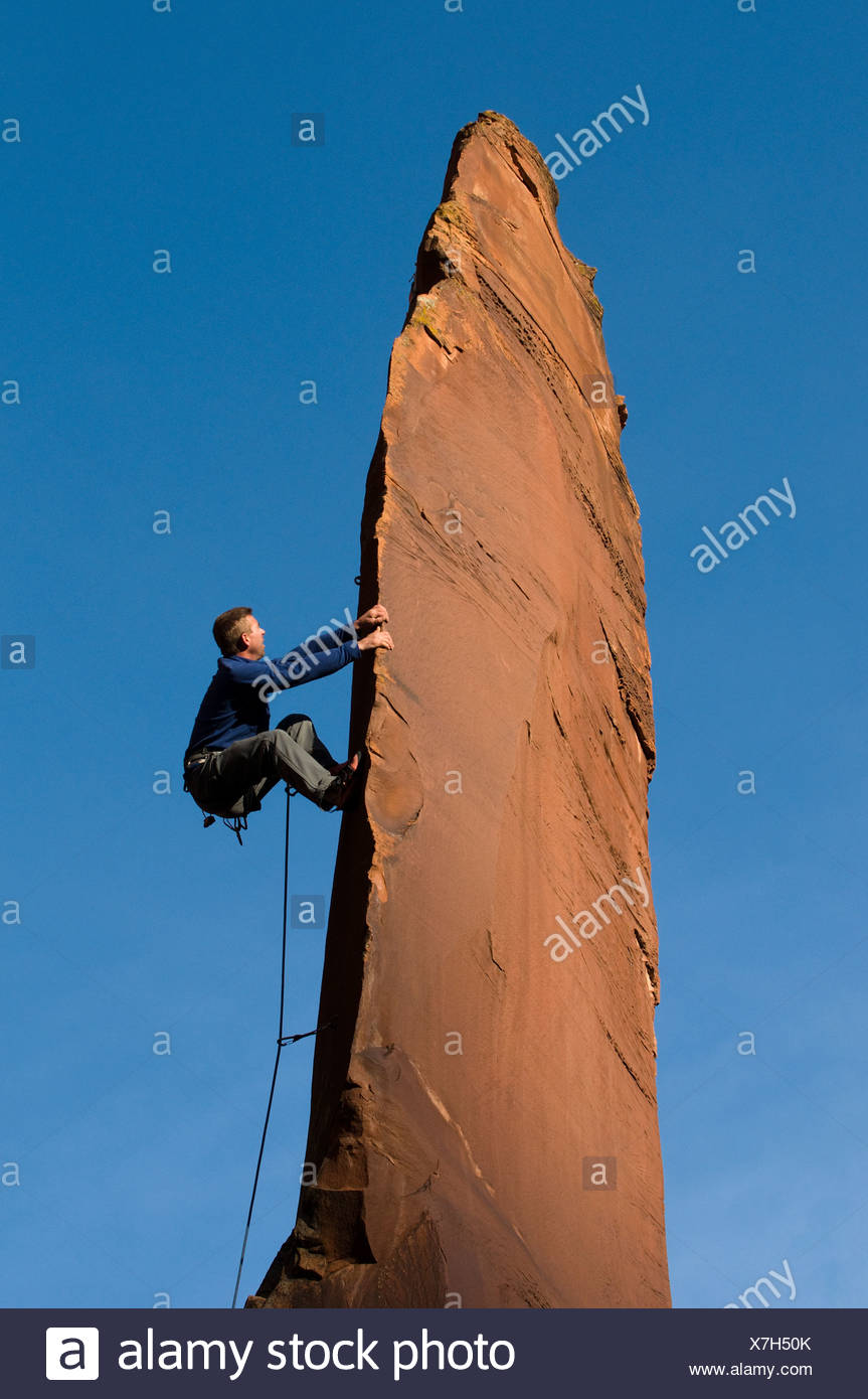 Man rock climbing up slender sandstone spire, Gateway, Colorado. - Stock Image