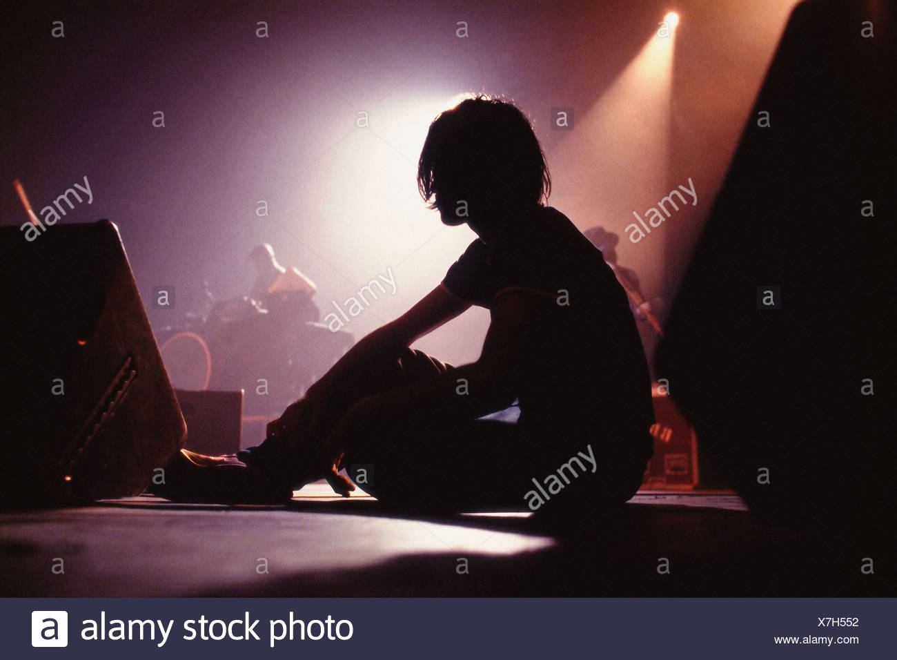 Silhouetted man sitting on stage - Stock Image