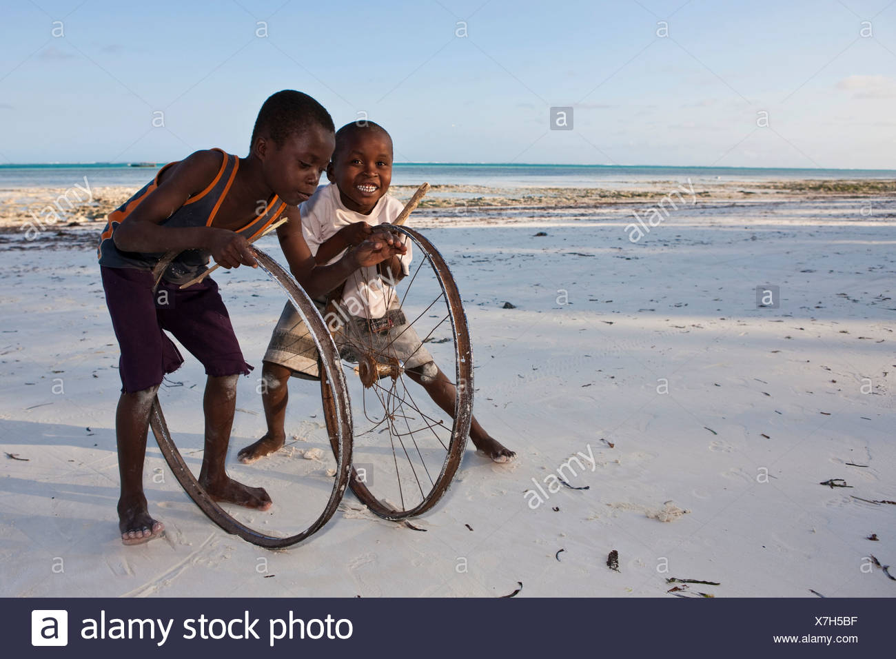 Children play with old bicycle wheels on the beach of Pingwe, Zanzibar, Tanzania, Africa - Stock Image