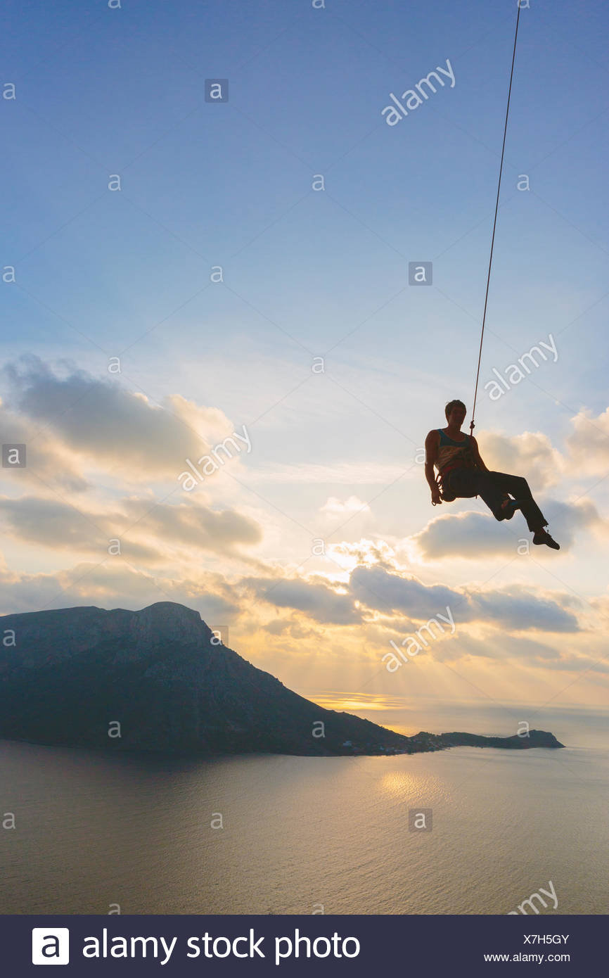 Greece, Dodecanese, Kalymnos, Man handing off climbing rope against sky - Stock Image