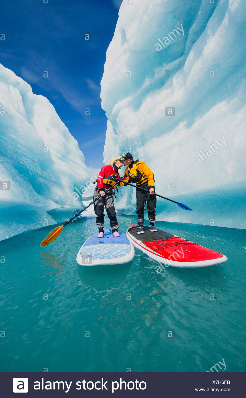 A couple on stand up paddle boards (SUP) kiss in an iceberg canyon on Bear Lake in Kenai Fjords National Park, Alaska. - Stock Image