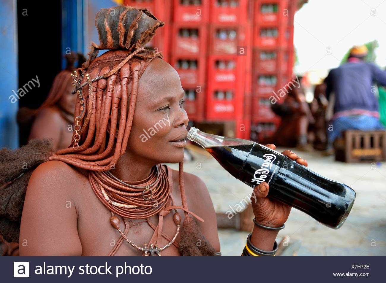 geography / travel, Namibia, traditional garb Himba woman drinking Coca Cola, bar 'Champ Style', Opuwo, Kaokoveld, Additional-Rights-Clearance-Info-Not-Available - Stock Image