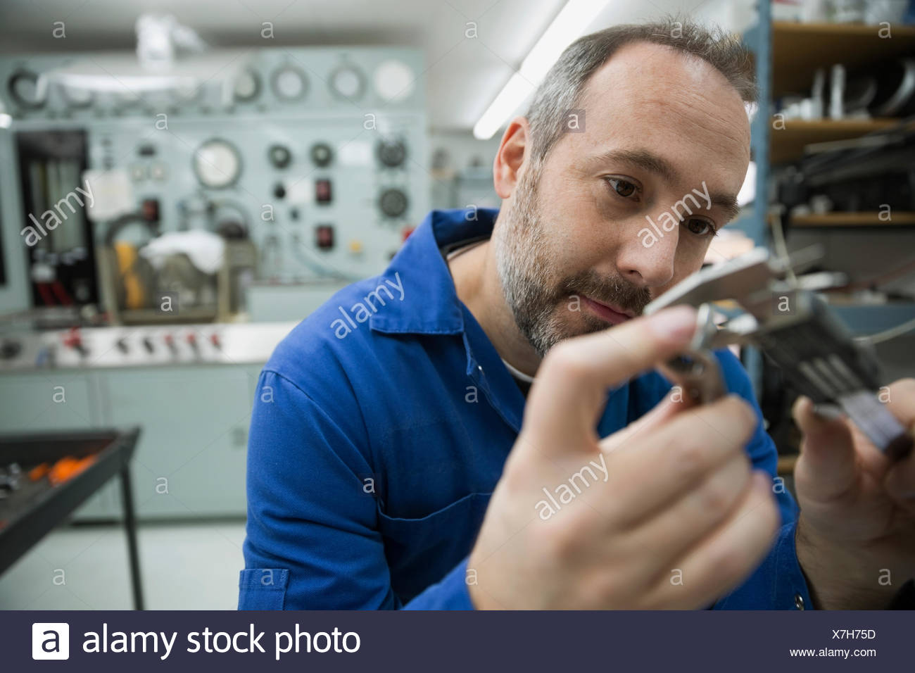 Helicopter mechanic examining part in workshop - Stock Image