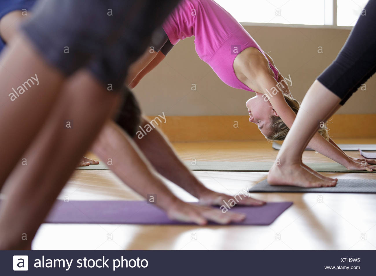 Mixed age and ethnicity group practicing yoga - Stock Image