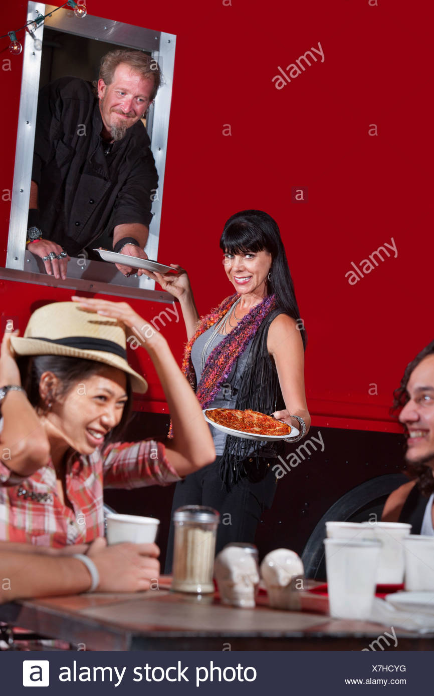 Lady Picking up Pizza Orders - Stock Image