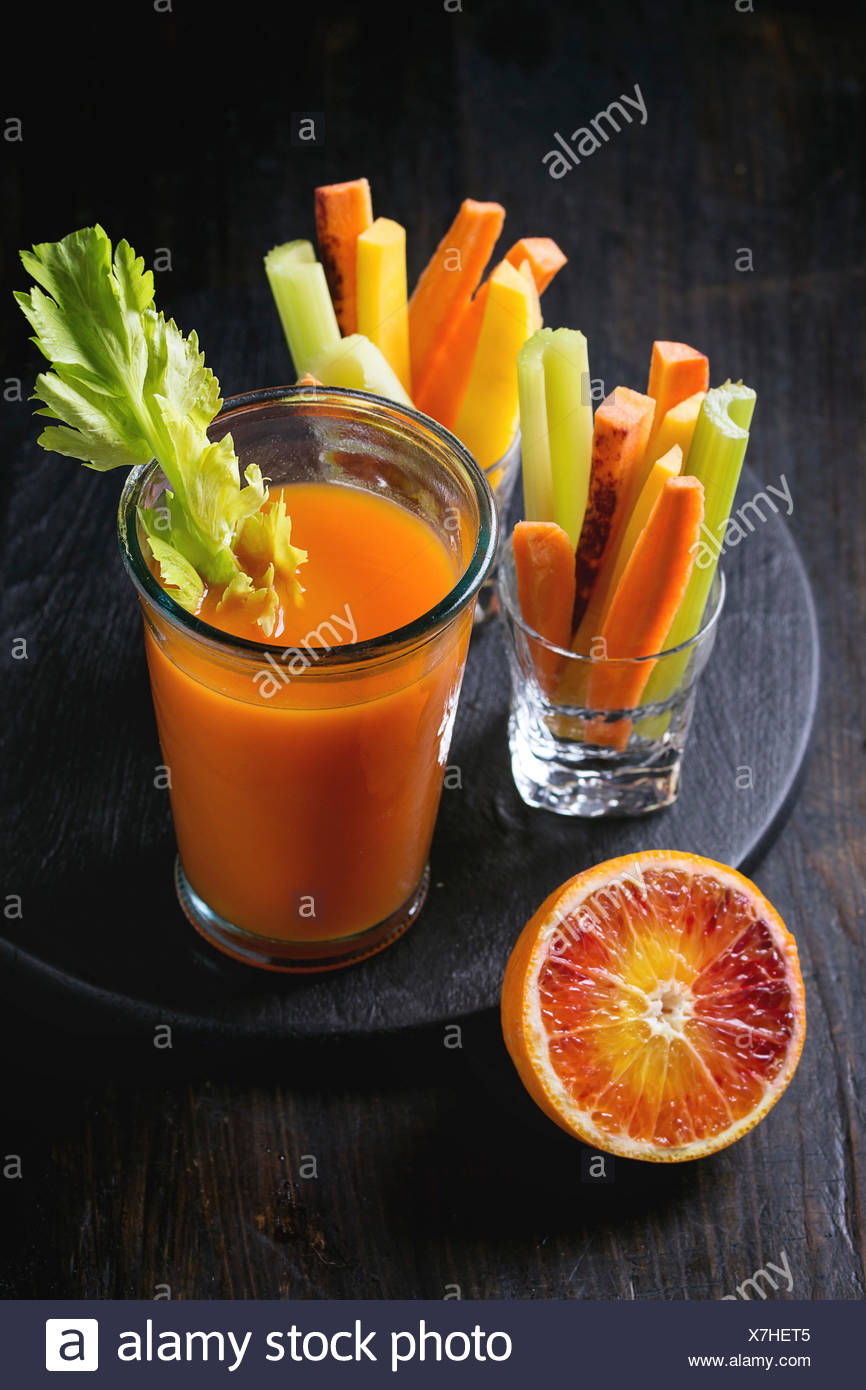 Sliced colorful raw carrots and celery as vegetarian snack, blood oranges with glass cup of fresh orange and carrot juice over b - Stock Image