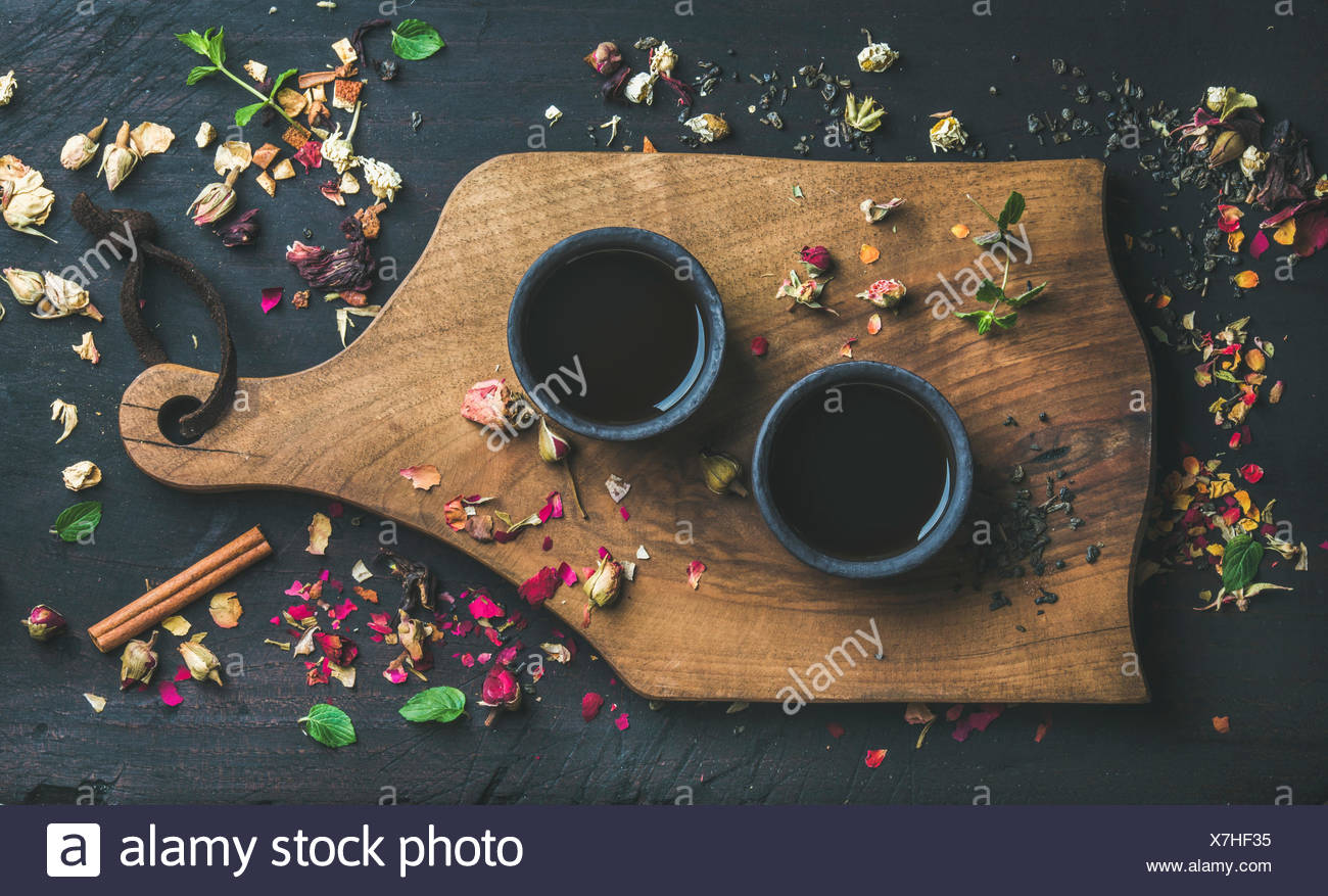 Chinese black tea in black stoneware cups on serving wooden board over black wooden background with herbs, flower buds, tea leaves spilt around, top v - Stock Image