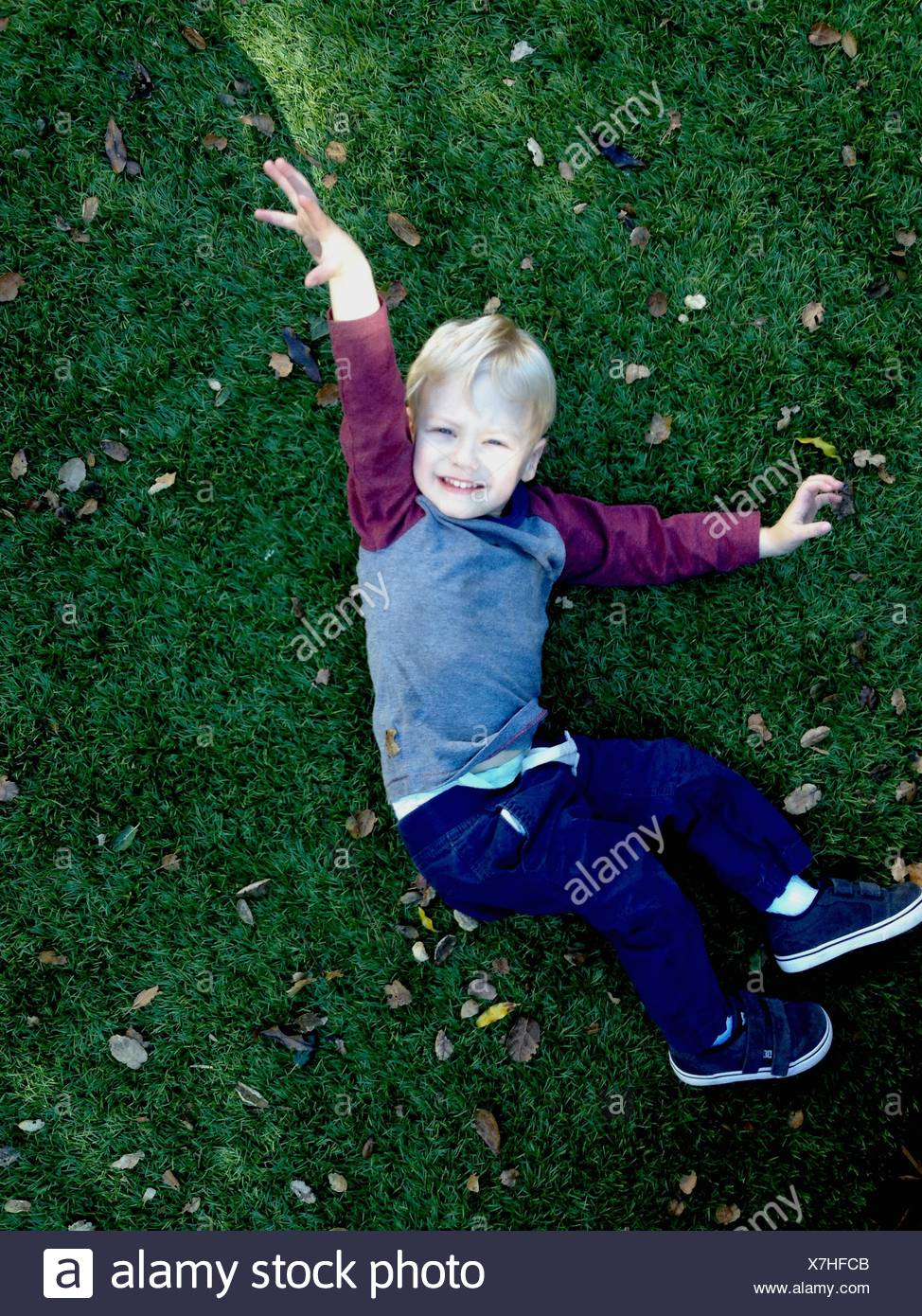 High Angle Portrait Of Smiling Cute Boy Relaxing On Grassy Field - Stock Image