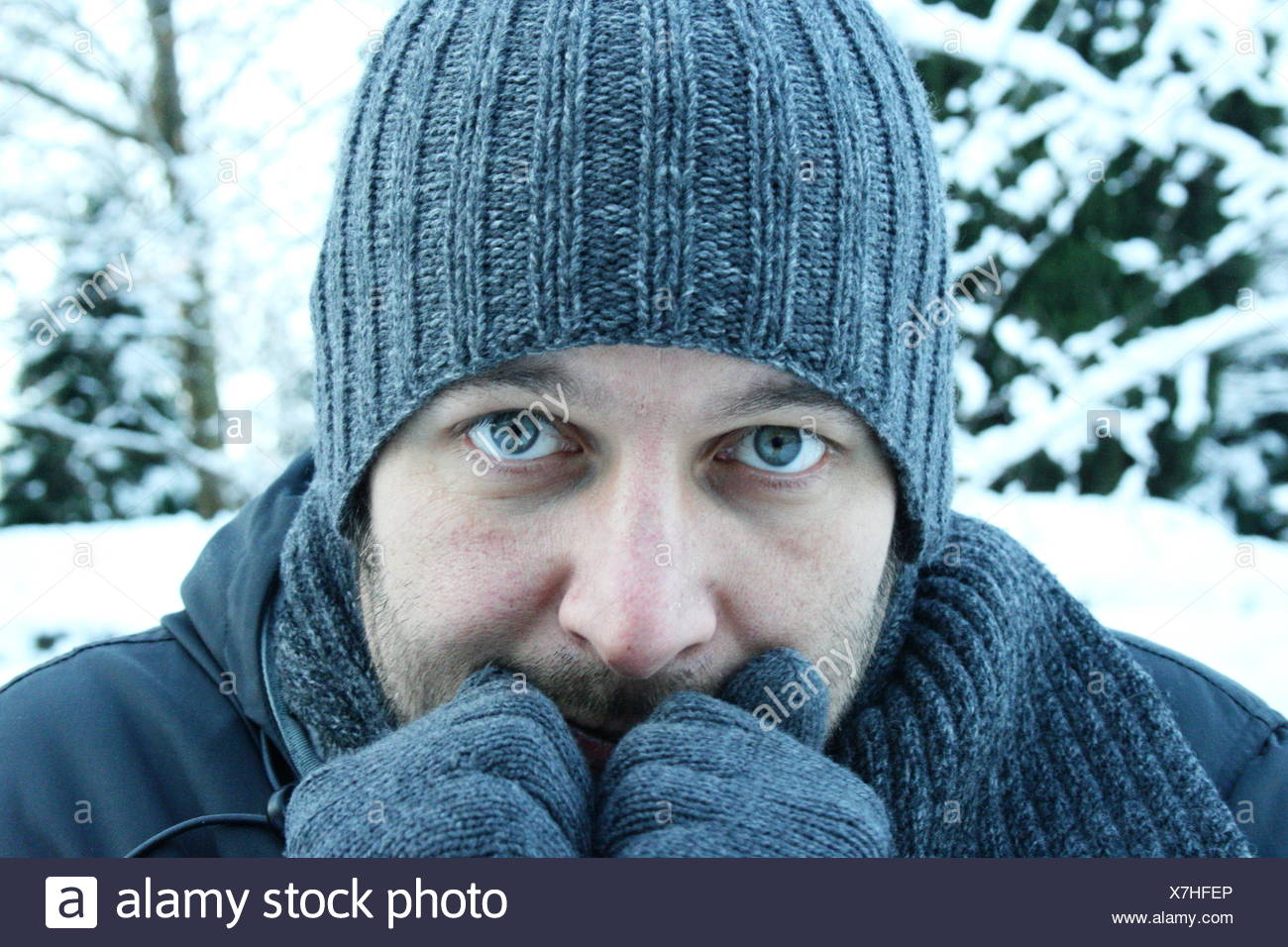 Portrait of a man in warm clothing shivering - Stock Image