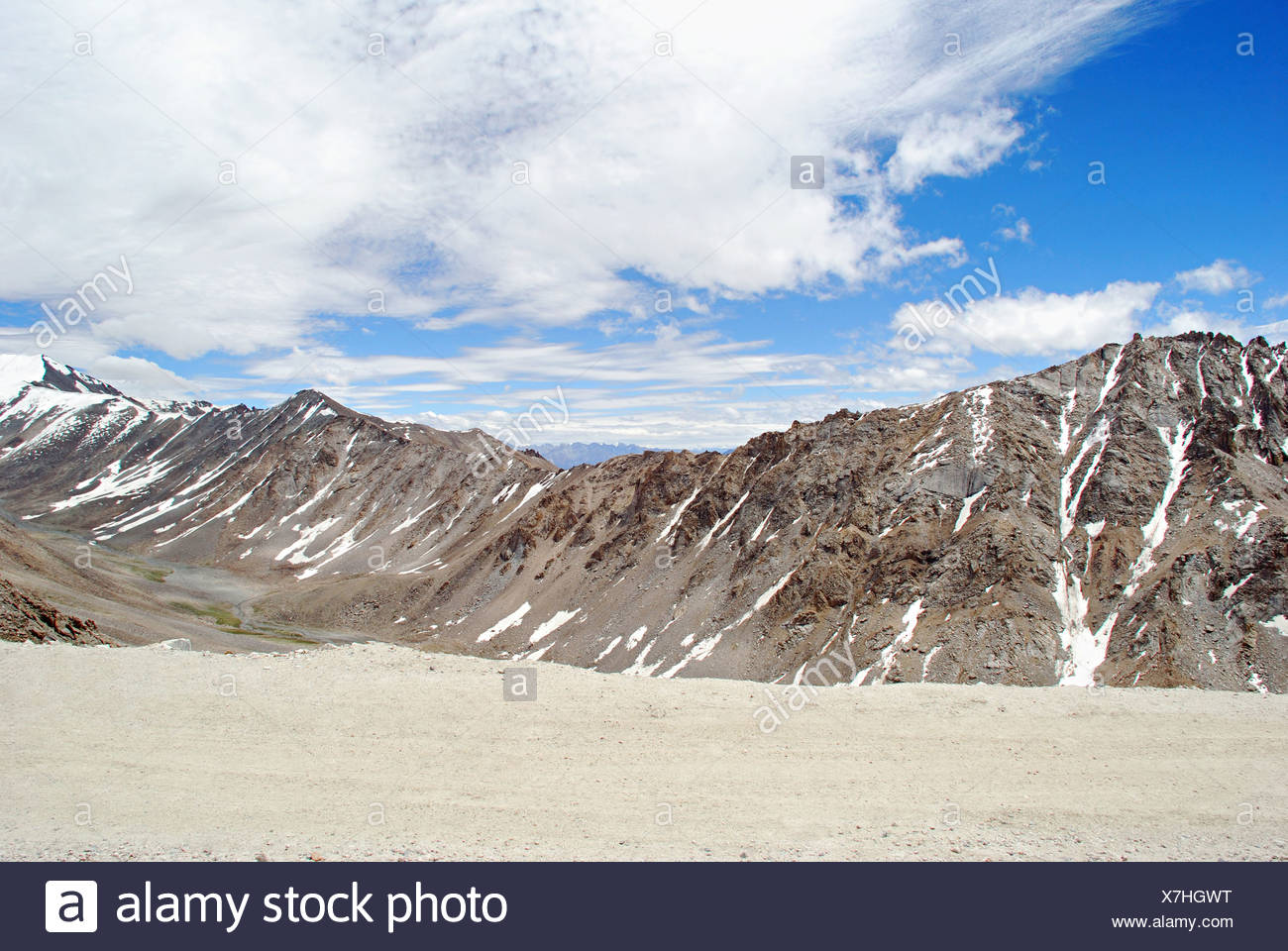 A road to Leh with snow clad Himalayan Mountain Ranges on both sides from the Changla Pass or Chang La Pass (el. 5,360 m (17,590 - Stock Image