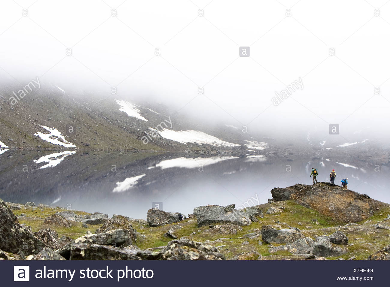 Mid distance shot of three people by the lake in the mist - Stock Image