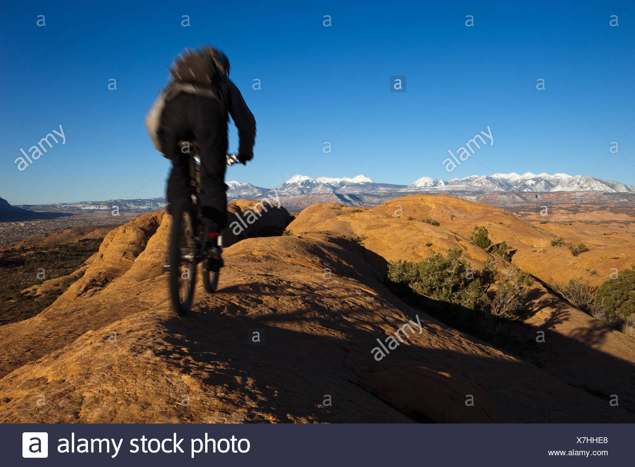 Mountain biker riding on the slickrock trail in Moab, Utah with views of faraway mountains. - Stock Image