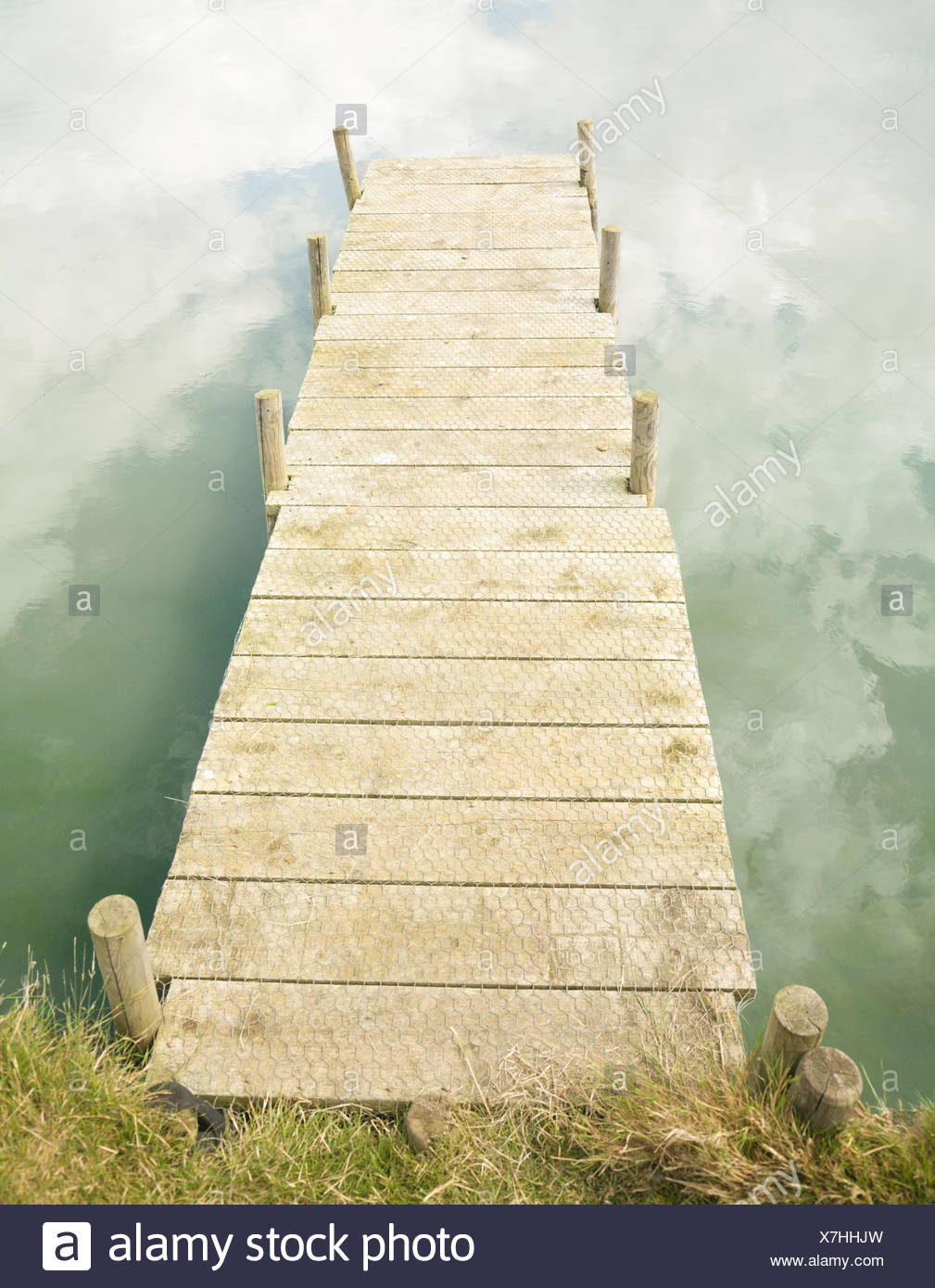 Jetty with cloud reflections - Stock Image