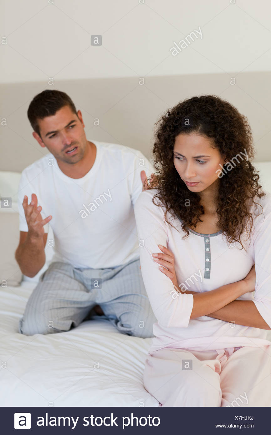 Young couple having a dispute on the bed - Stock Image