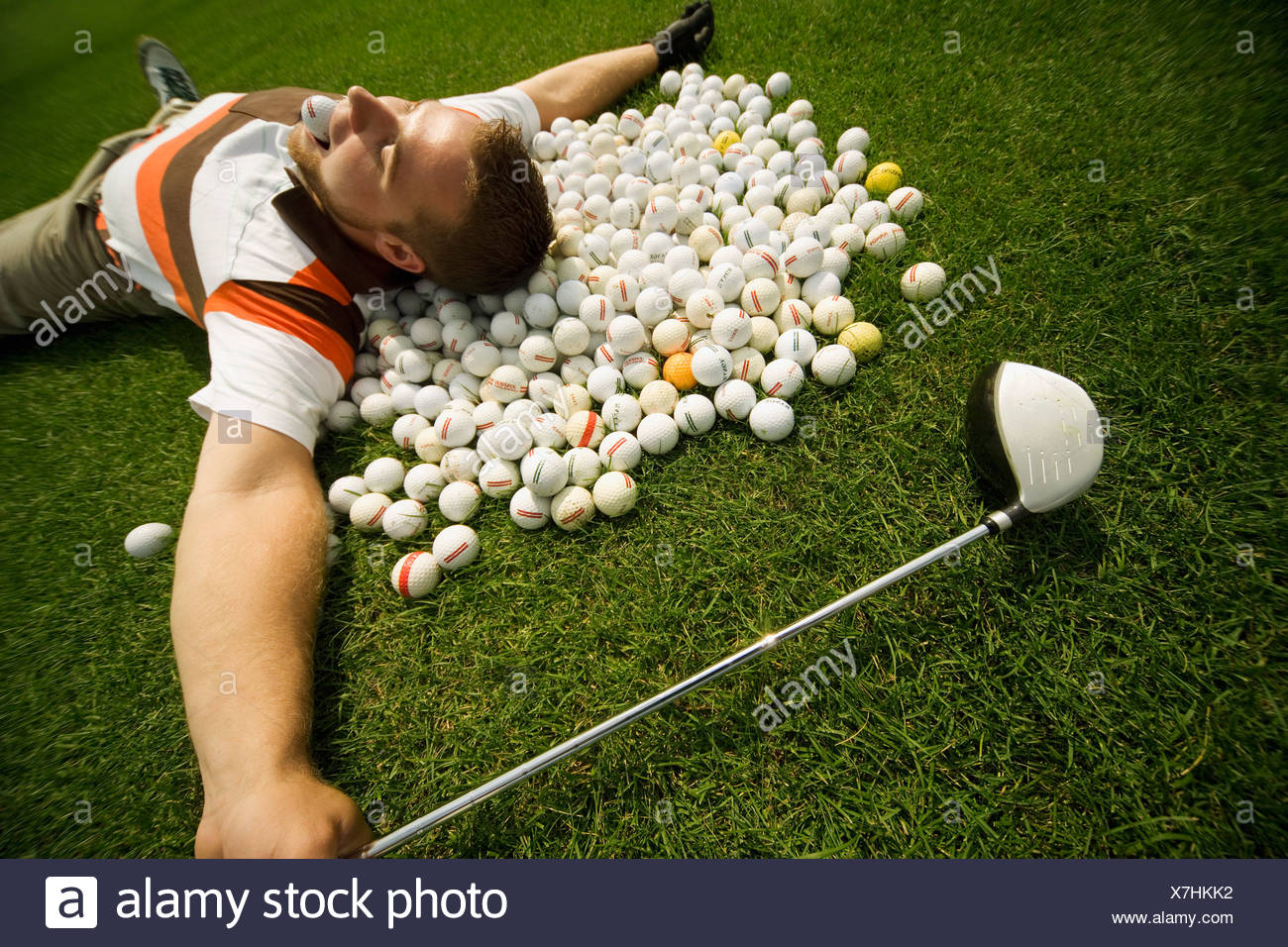 A man lying on golf balls - Stock Image