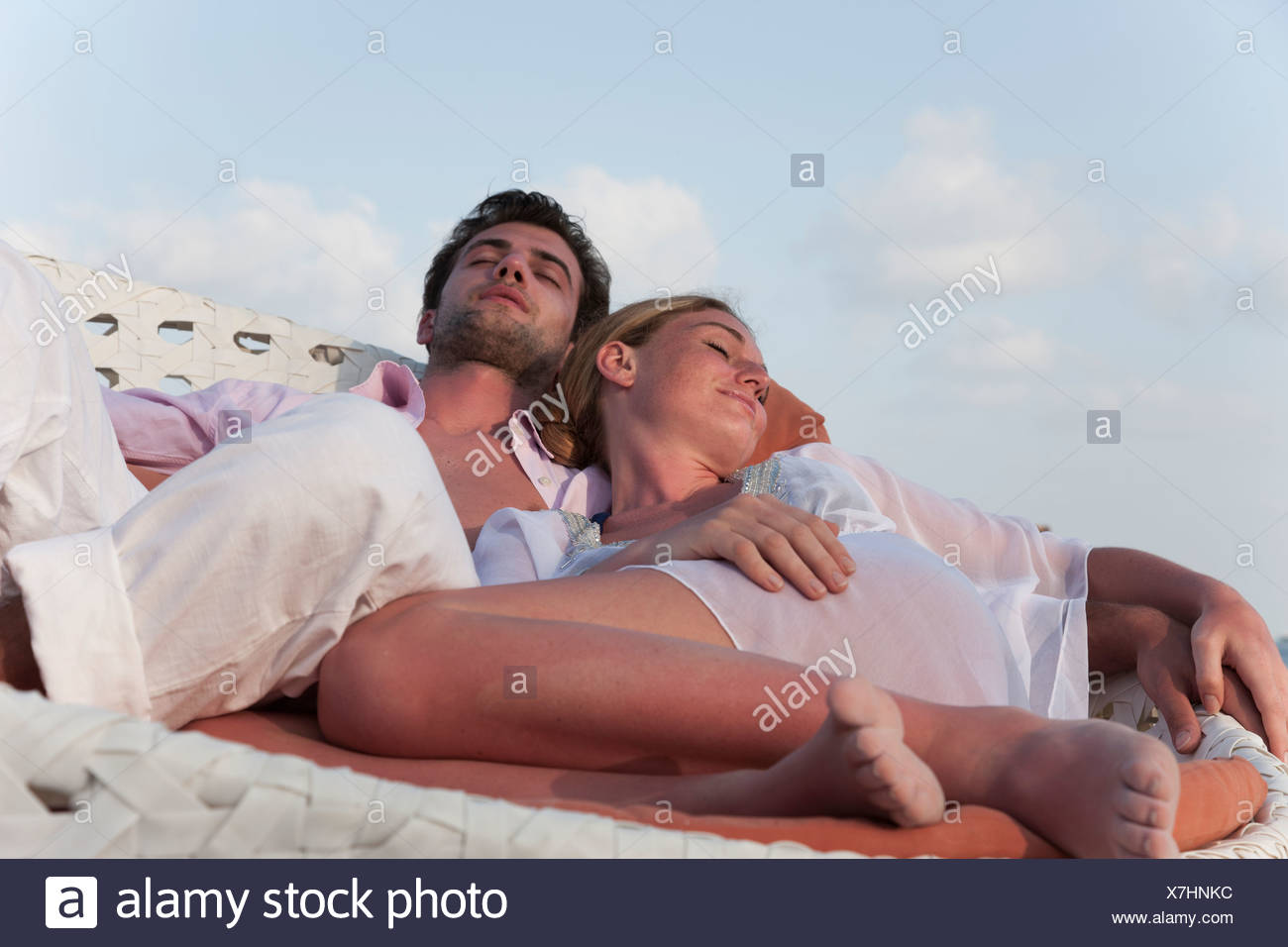 Couple sleeping in wicker chair - Stock Image