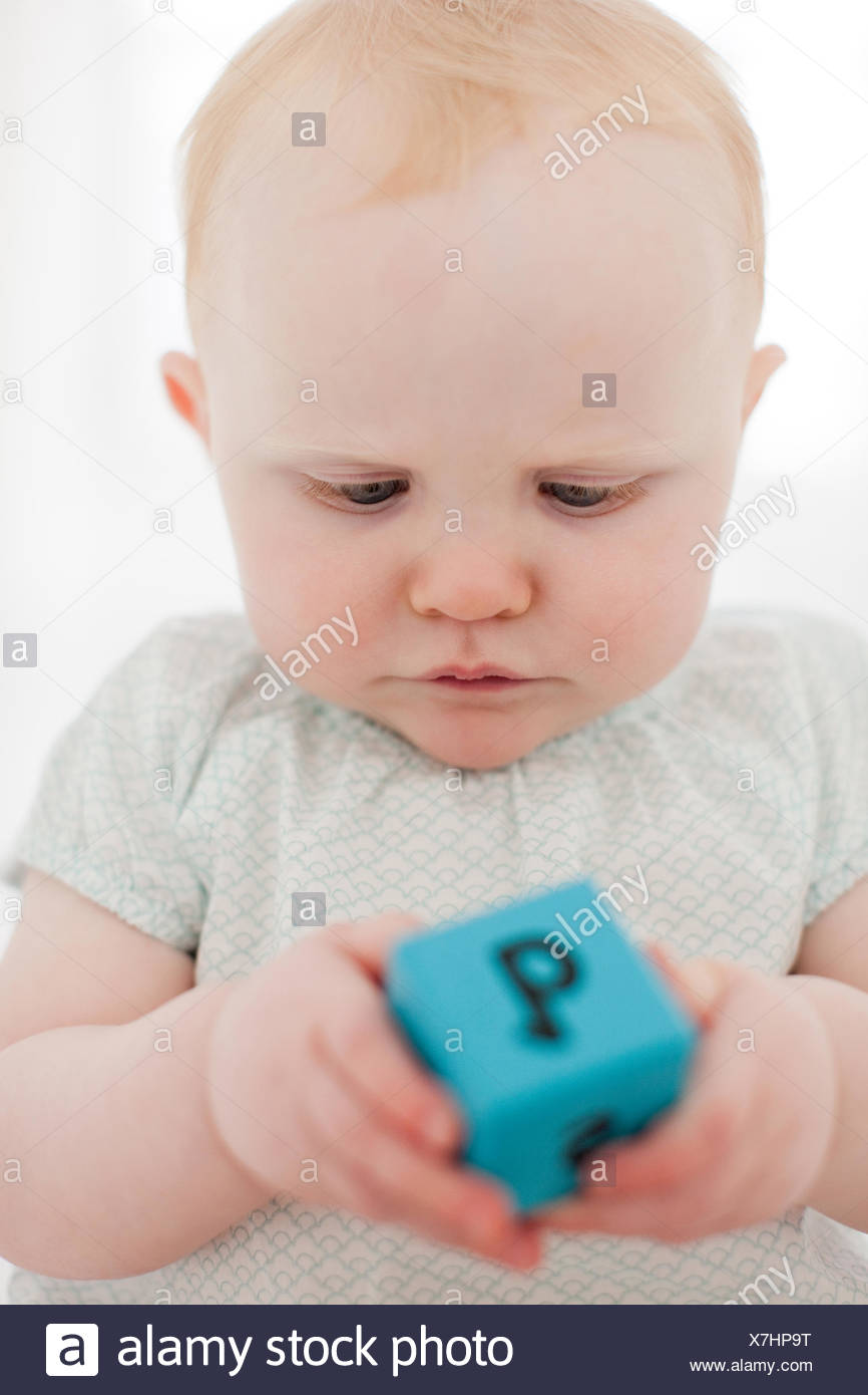 Close up of baby playing wood block - Stock Image
