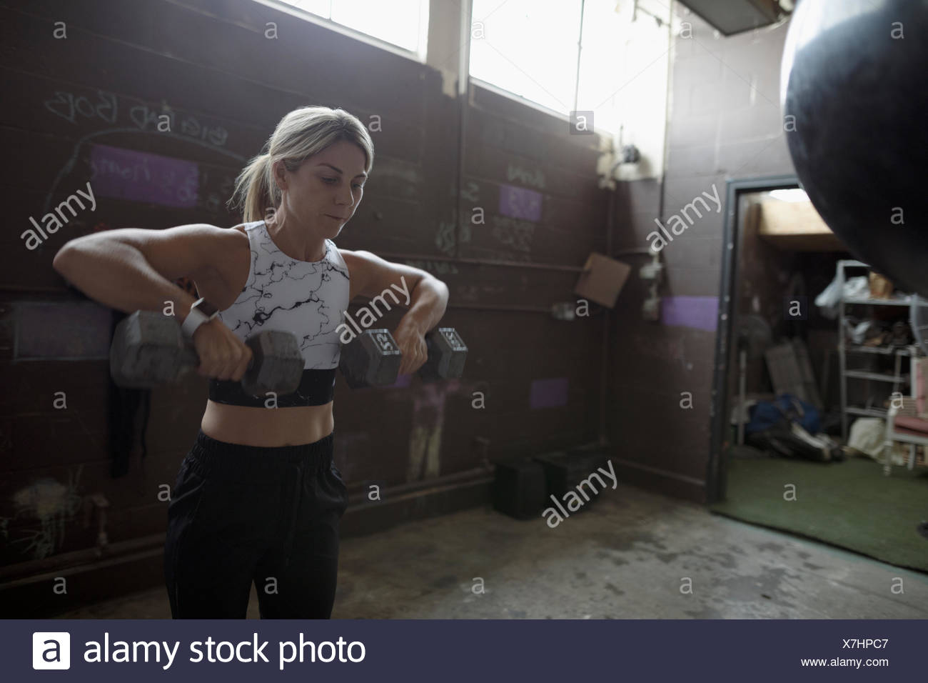 Woman weightlifting with dumbbells in gritty gym - Stock Image