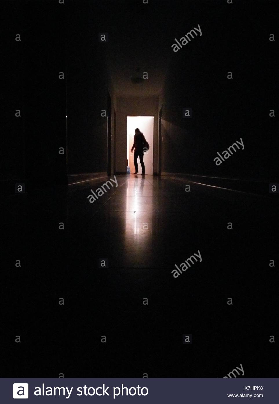 Silhouette Person In Corridor Entering Illuminated Room - Stock Image