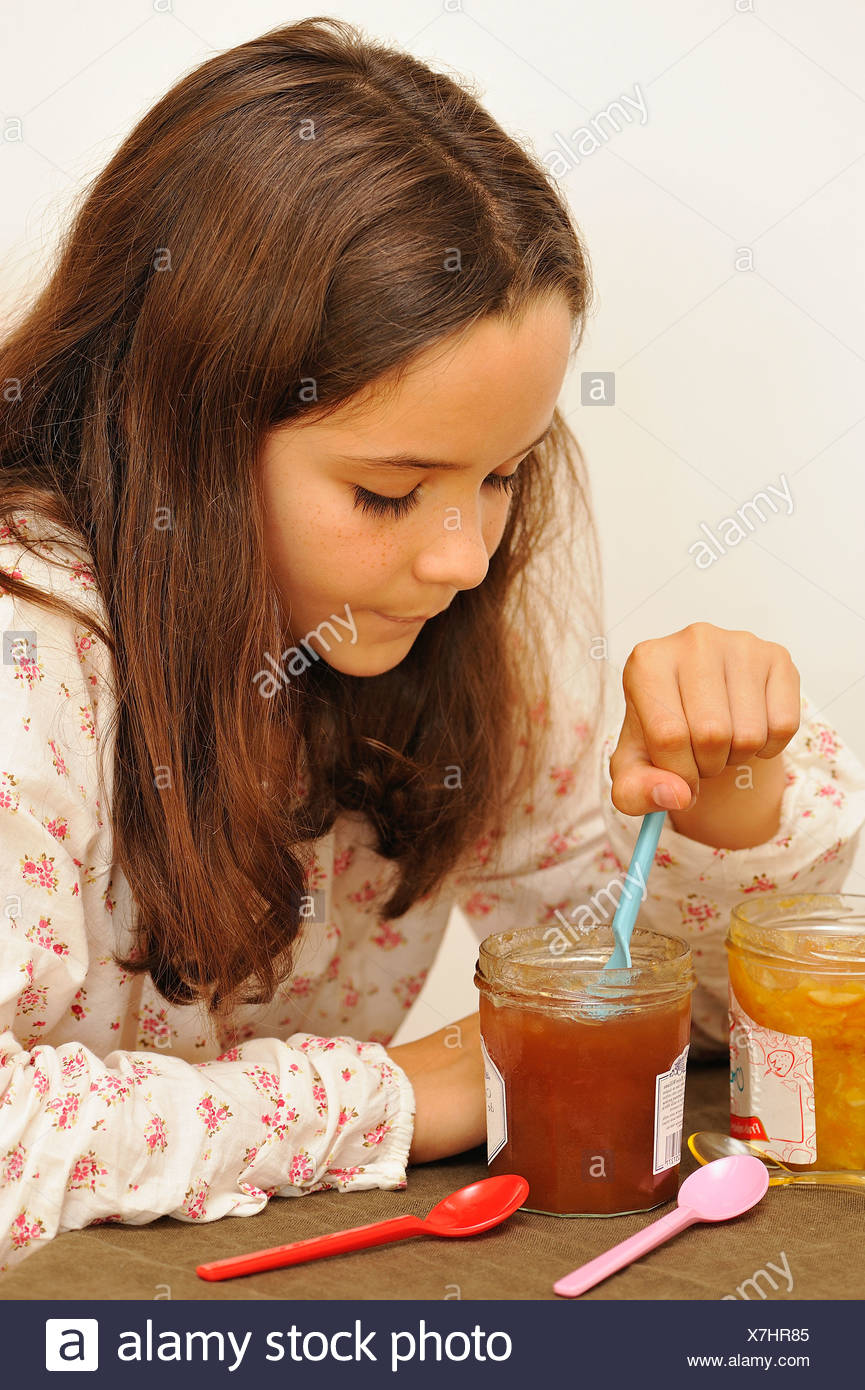 Young Girl Taking A Spoonful Of Jam