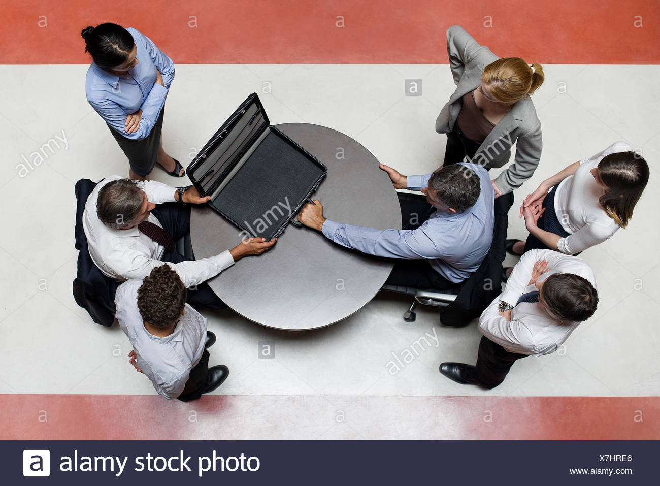 Businessman flanked by support staff tempted by opponents offered deal - Stock Image