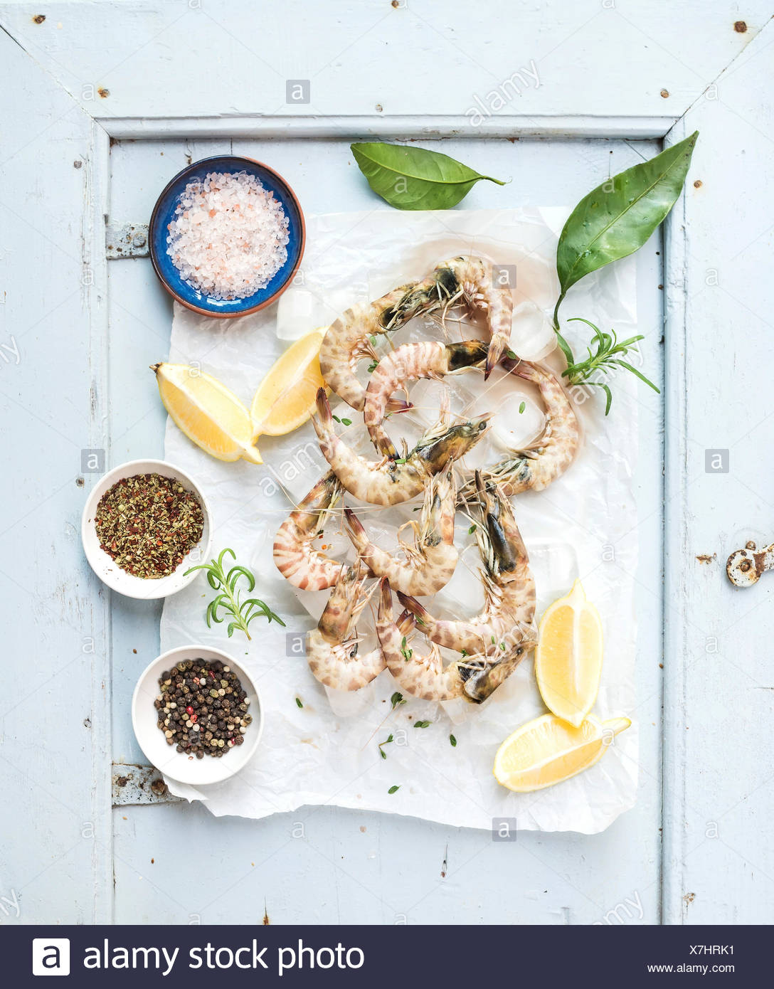 Fresh uncooked shrimps with lemon, herbs, ice and spices on rustic blue wooden board backdrop, top view - Stock Image