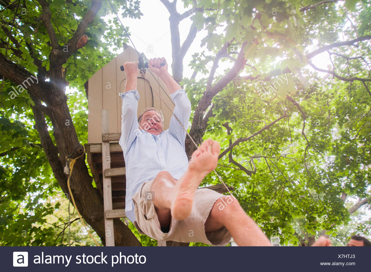 Mature man sliding down on pulley from tree house Stock Photo