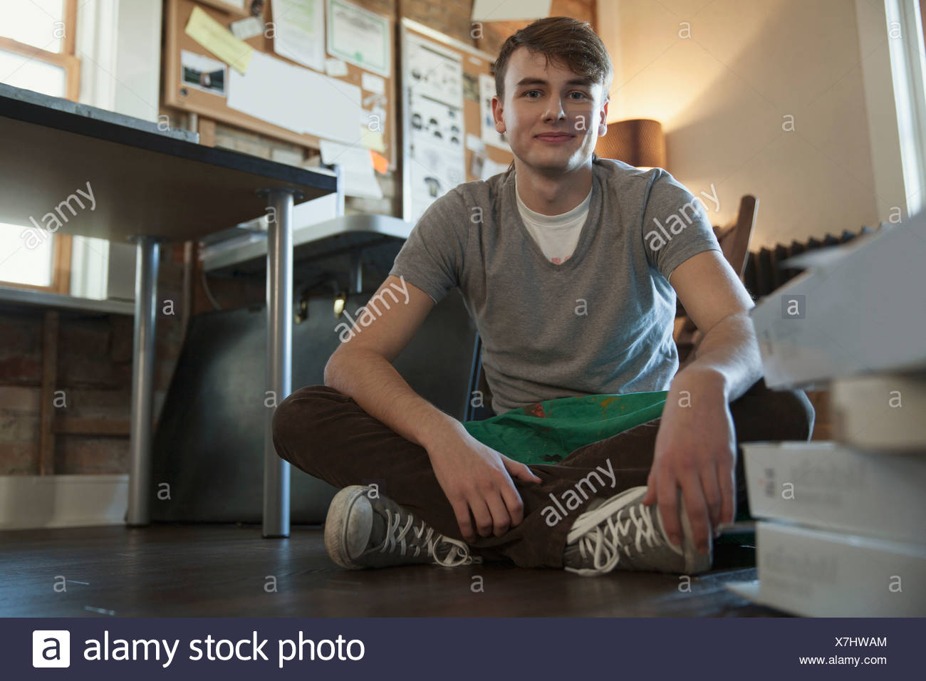 Portrait of young male design professional sitting on floor at workshop Stock Photo