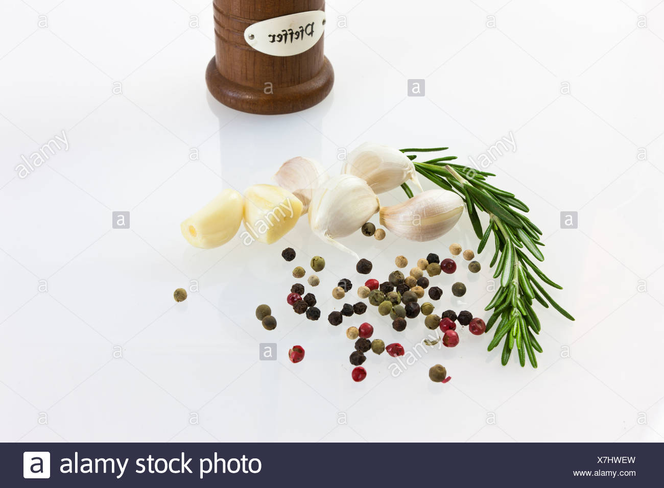 Garlic (Allium sativum) with pepper mill, fresh rosemary, black and red pepper - Stock Image
