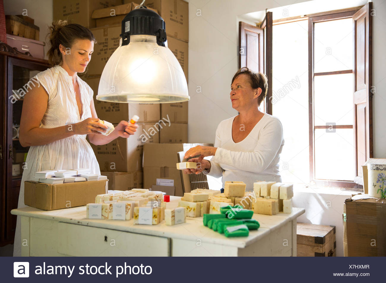 Two women packing soap products in handmade soap workshop Stock Photo