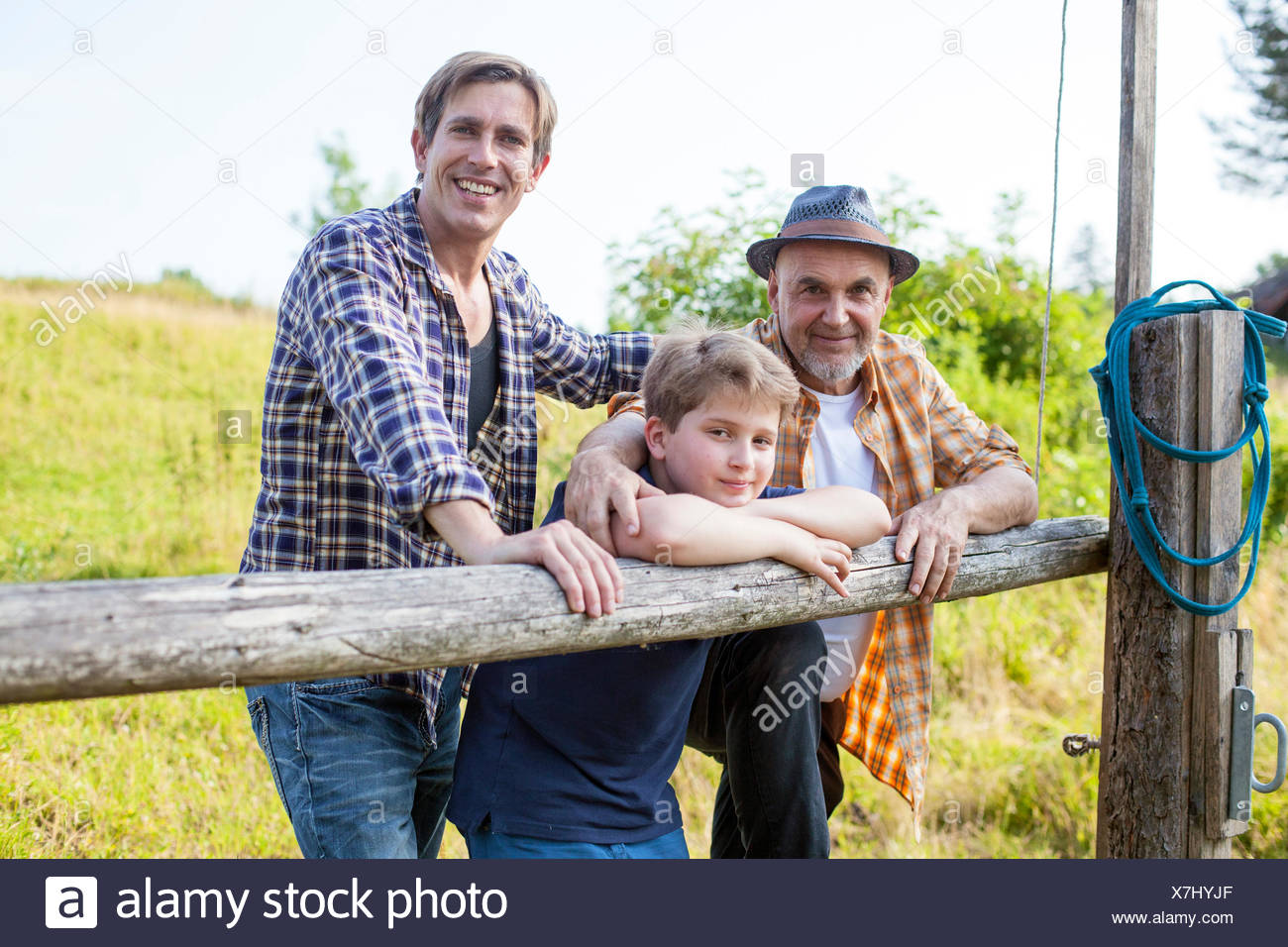Portrait of multi-generation family by fence - Stock Image