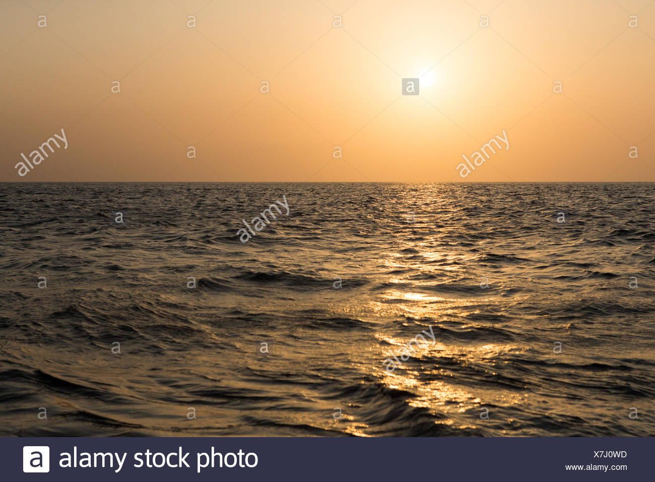 In Gulf of Panama waters,near Bona Island,the sun rises on a misty,hazy morning and reflects light off of choppy waters. - Stock Image