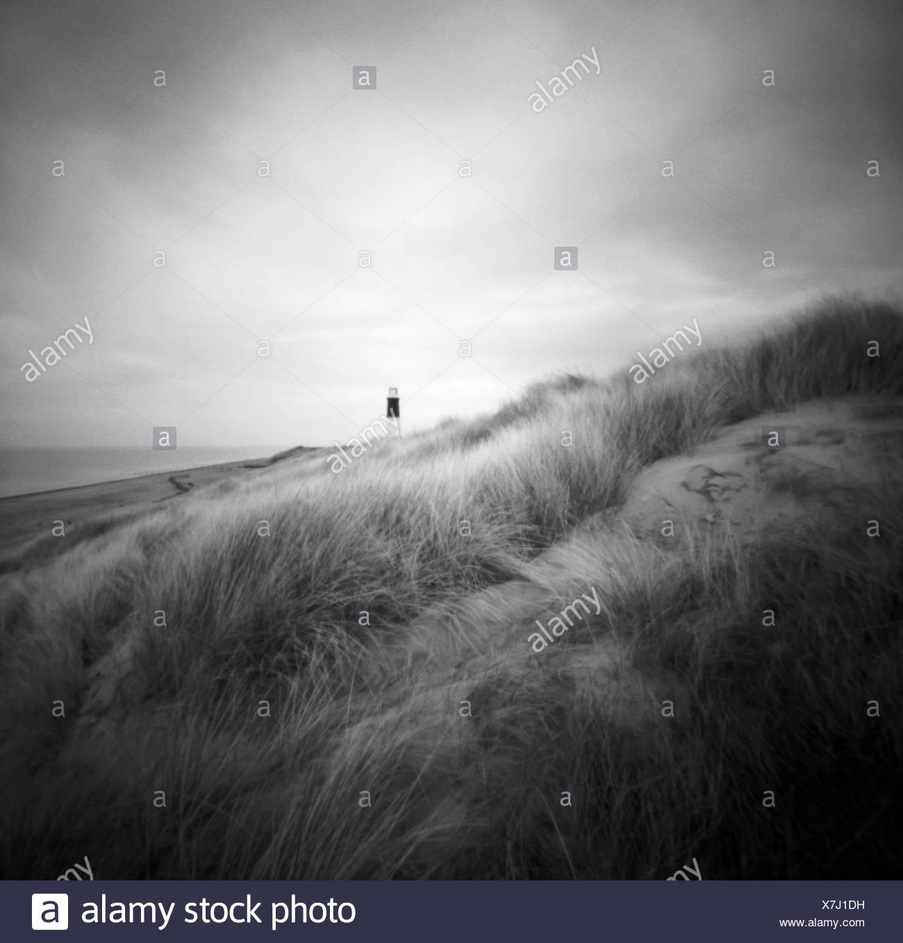 Single figure on sand banks at Seashore Spurn Head Point Lighthouse, East Yorkshire, England - Stock Image