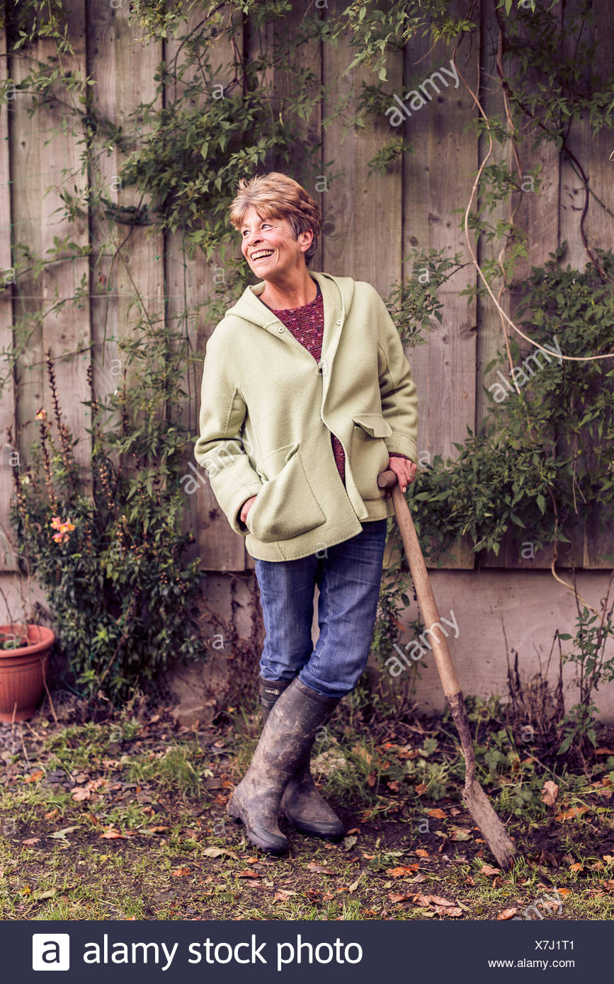 Portrait of mature woman leaning on spade in garden - Stock Image