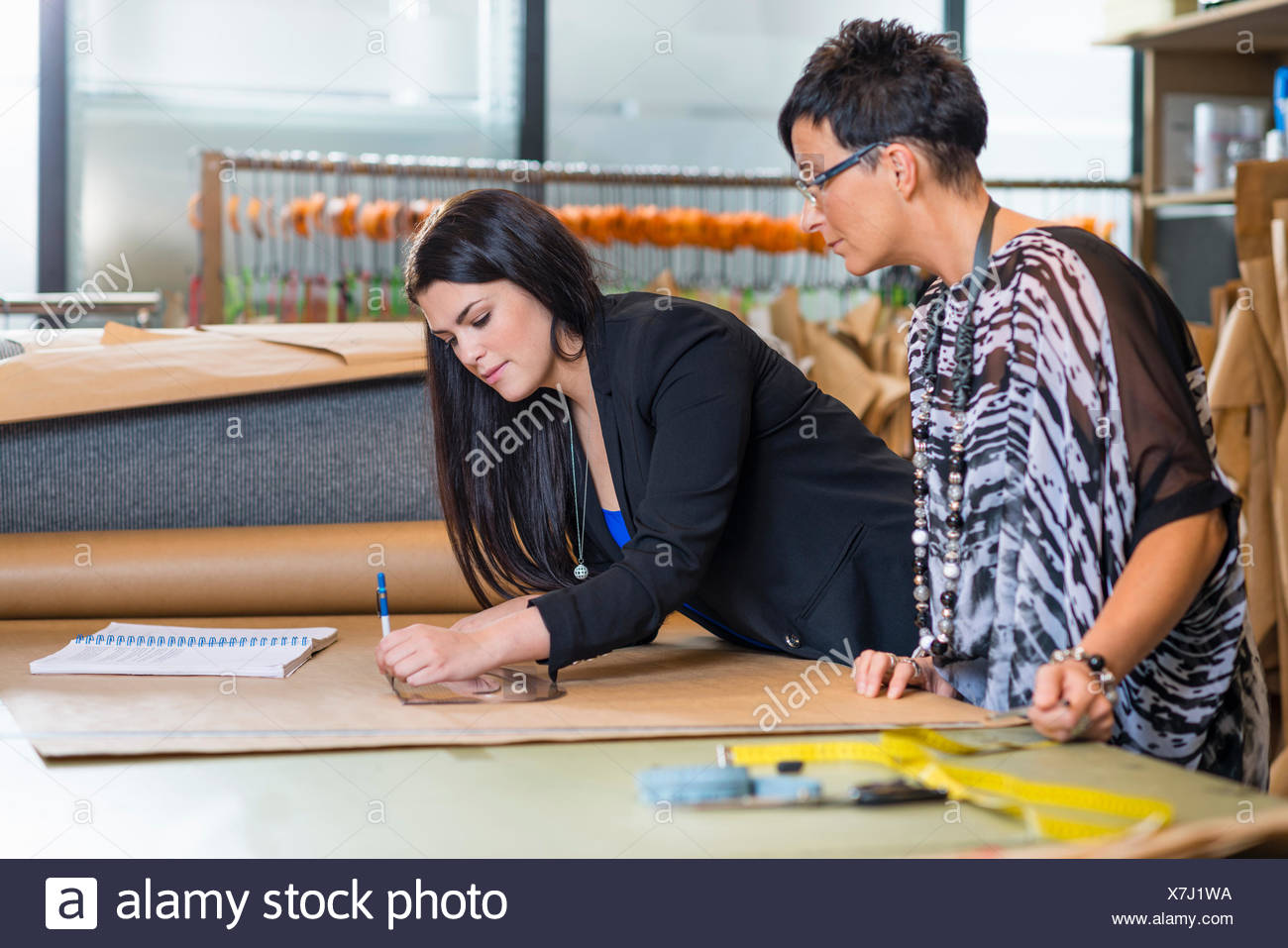 Two seamstresses drawing dressmakers pattern in workshop - Stock Image