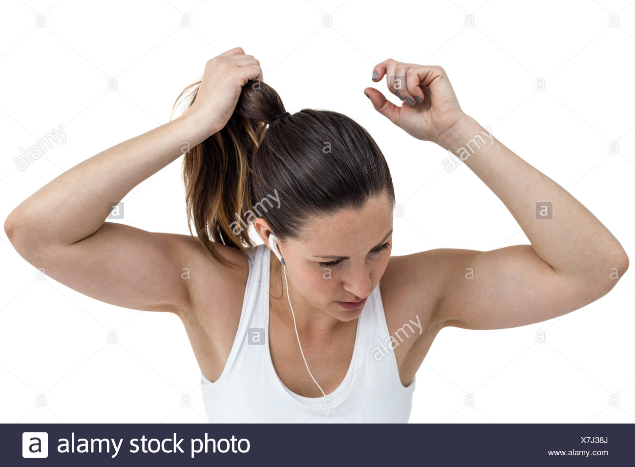 Athlete woman tying her hair and listening to music - Stock Image