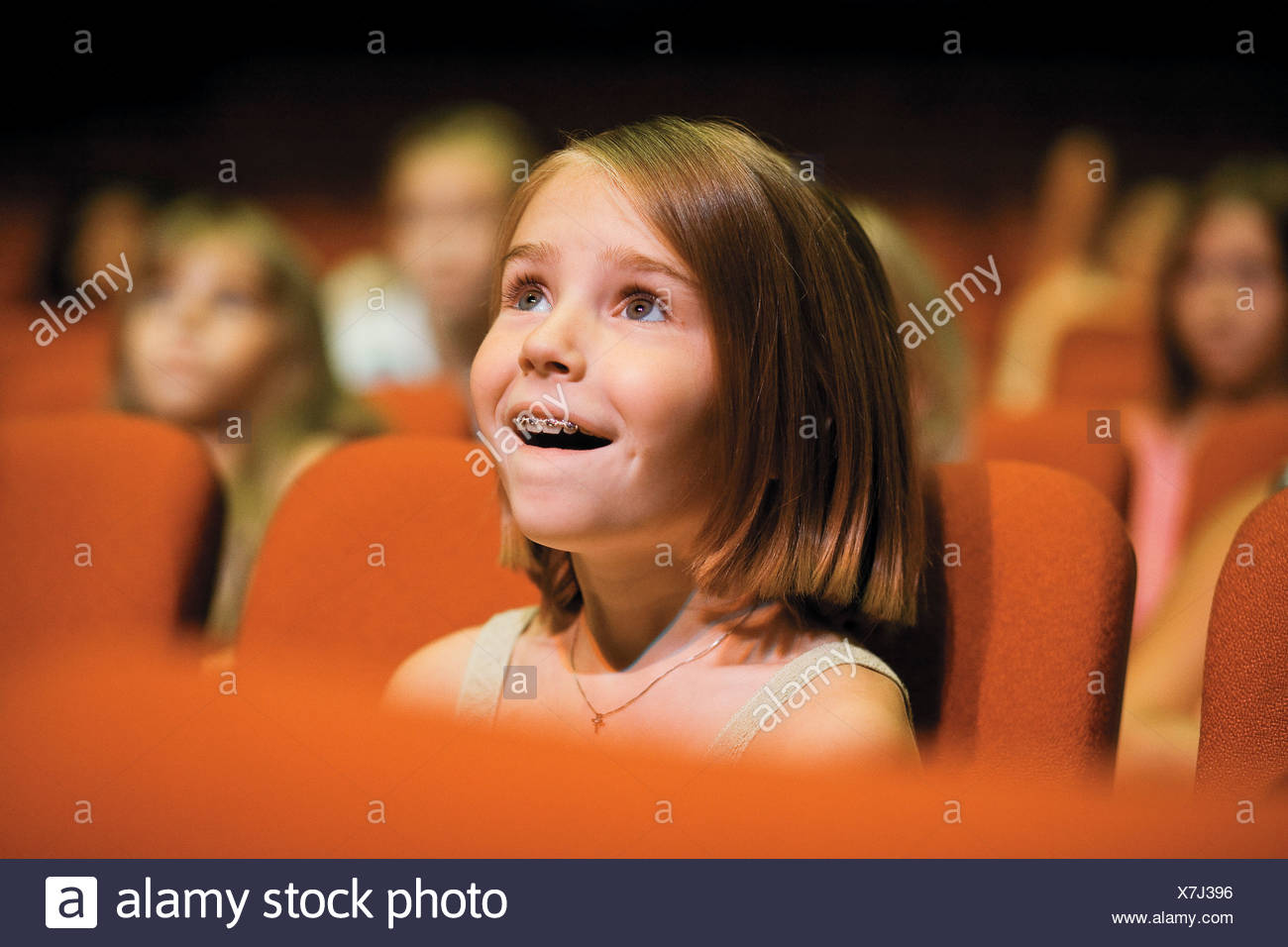 Girl sitting in theatre seat - Stock Image
