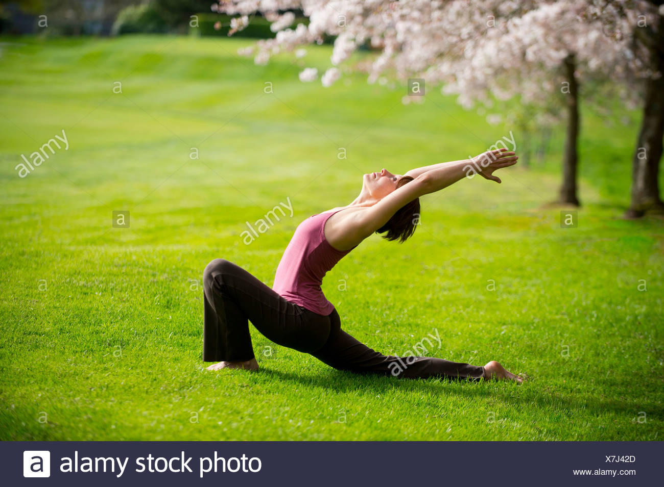 Woman in crescent moon yoga position in park - Stock Image
