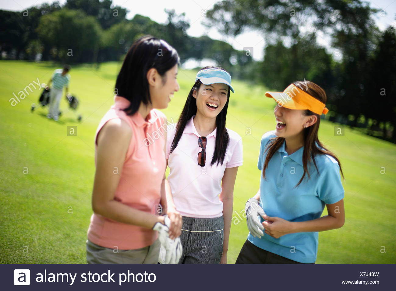 Three women playing golf with man in background - Stock Image