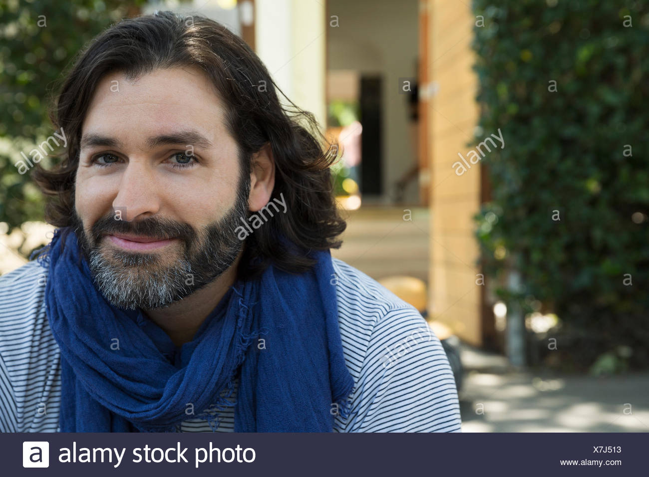 Portrait of smiling man with beard wearing scarf - Stock Image