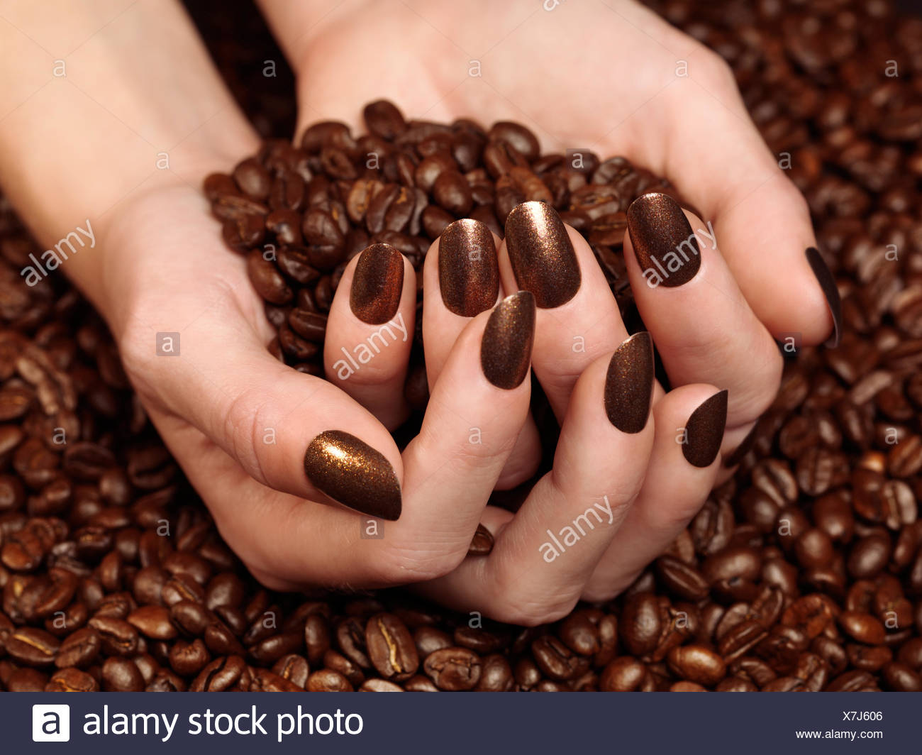 Woman's hands holding coffee beans in her hands, with matching brown nail polish - Stock Image