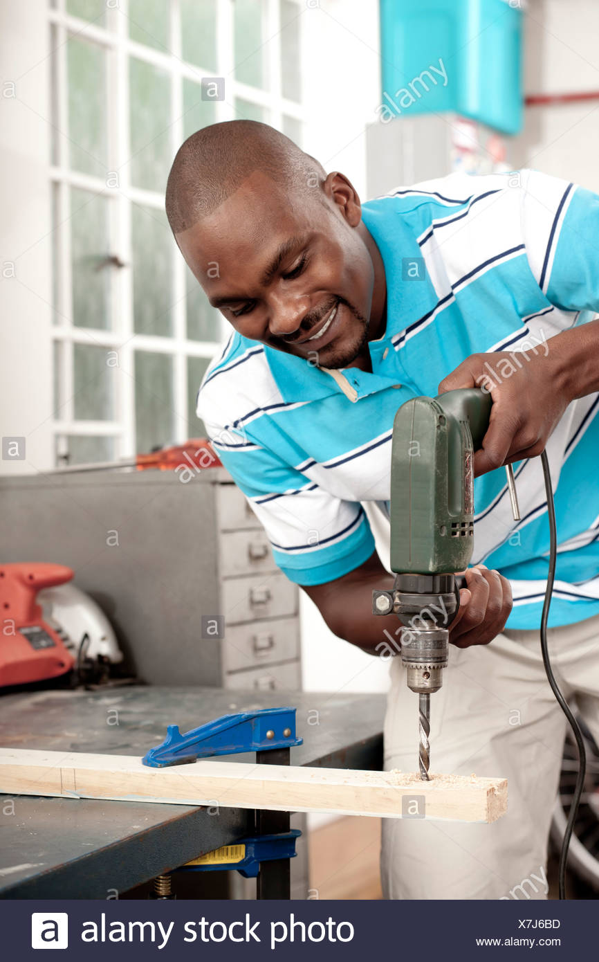 African man using drill in a workshop - Stock Image