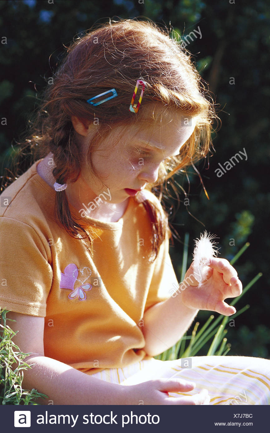 Girls, bird's feather, look, seriously, half portrait, side view, summers, child, red-haired, plaits, freckles, 6 years, sadly, thoughtful, pious, submergedly, lost in thought, affected, suppressed, only, feather, look, mood, devotion, grief, contemplatio - Stock Image