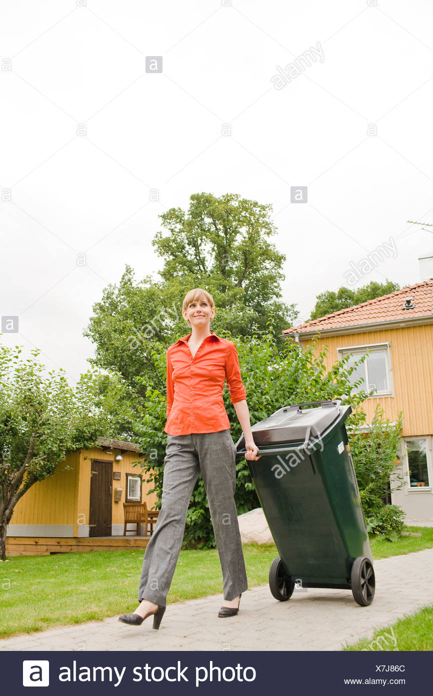 A woman pulling a refuse bin, Sweden. - Stock Image