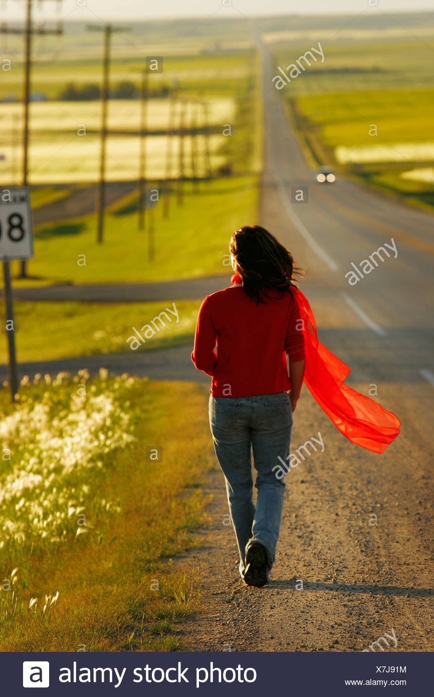 Woman walking along highway surrounded by fields - Stock Image