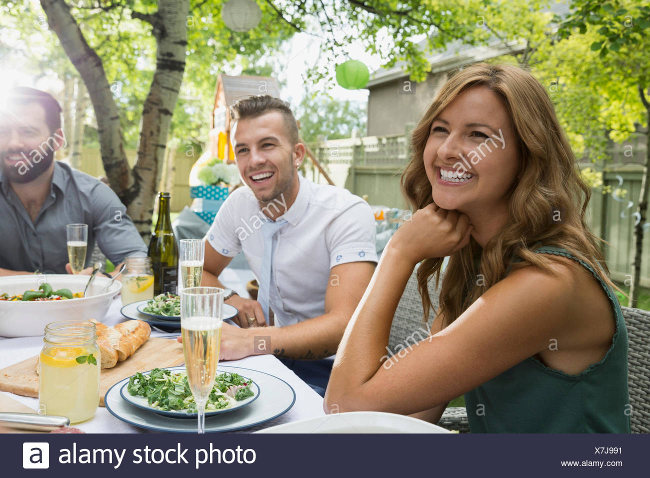 Smiling friends enjoying garden party lunch - Stock Image