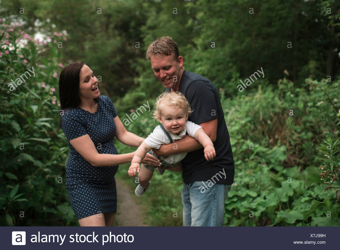 Pregnant couple swinging toddler son on pathway Stock Photo