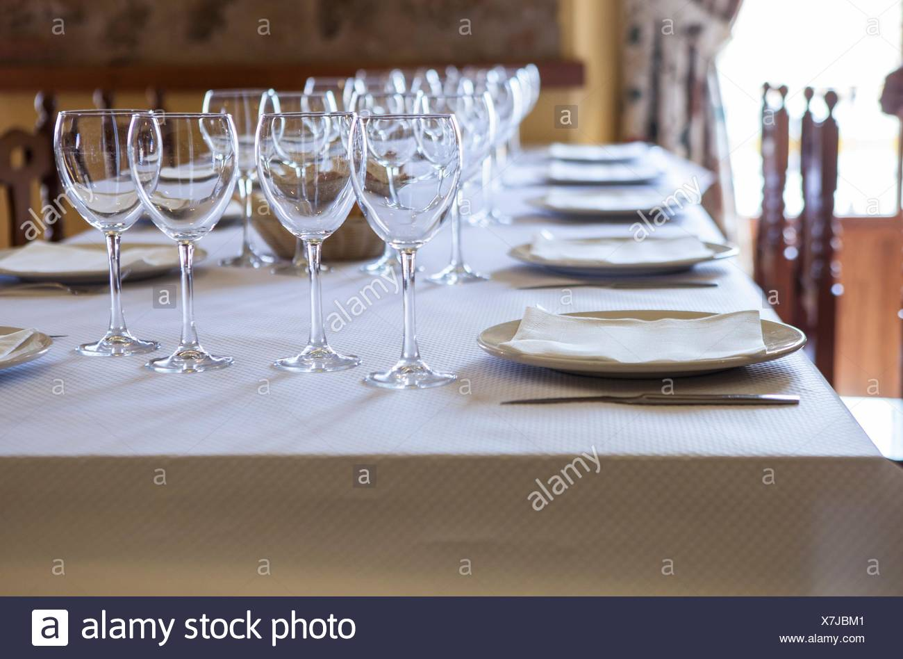 Tables ready and waiting for the guests to arrive at a rustic restaurant. - Stock Image