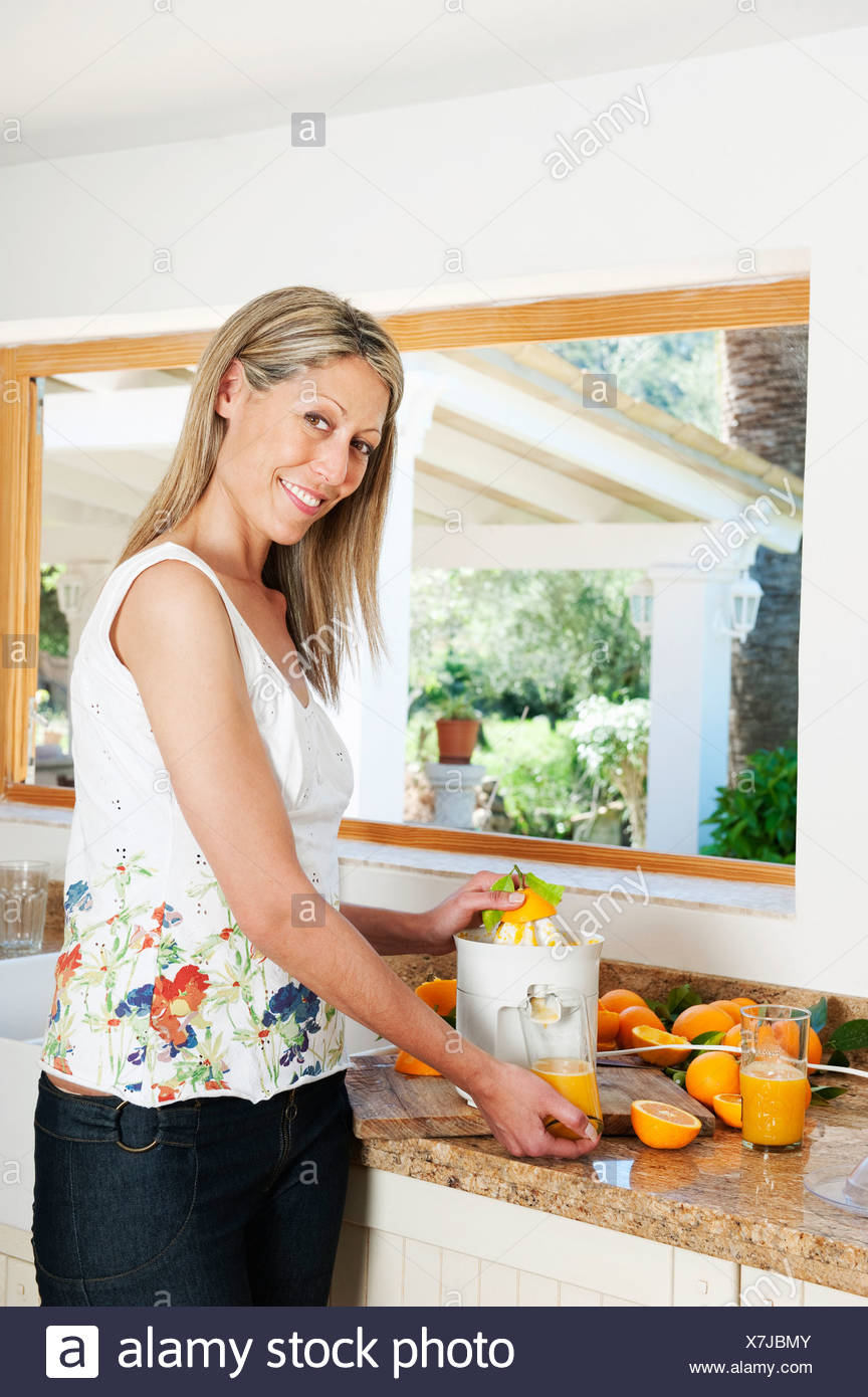 Woman using a juicer in kitchen Stock Photo