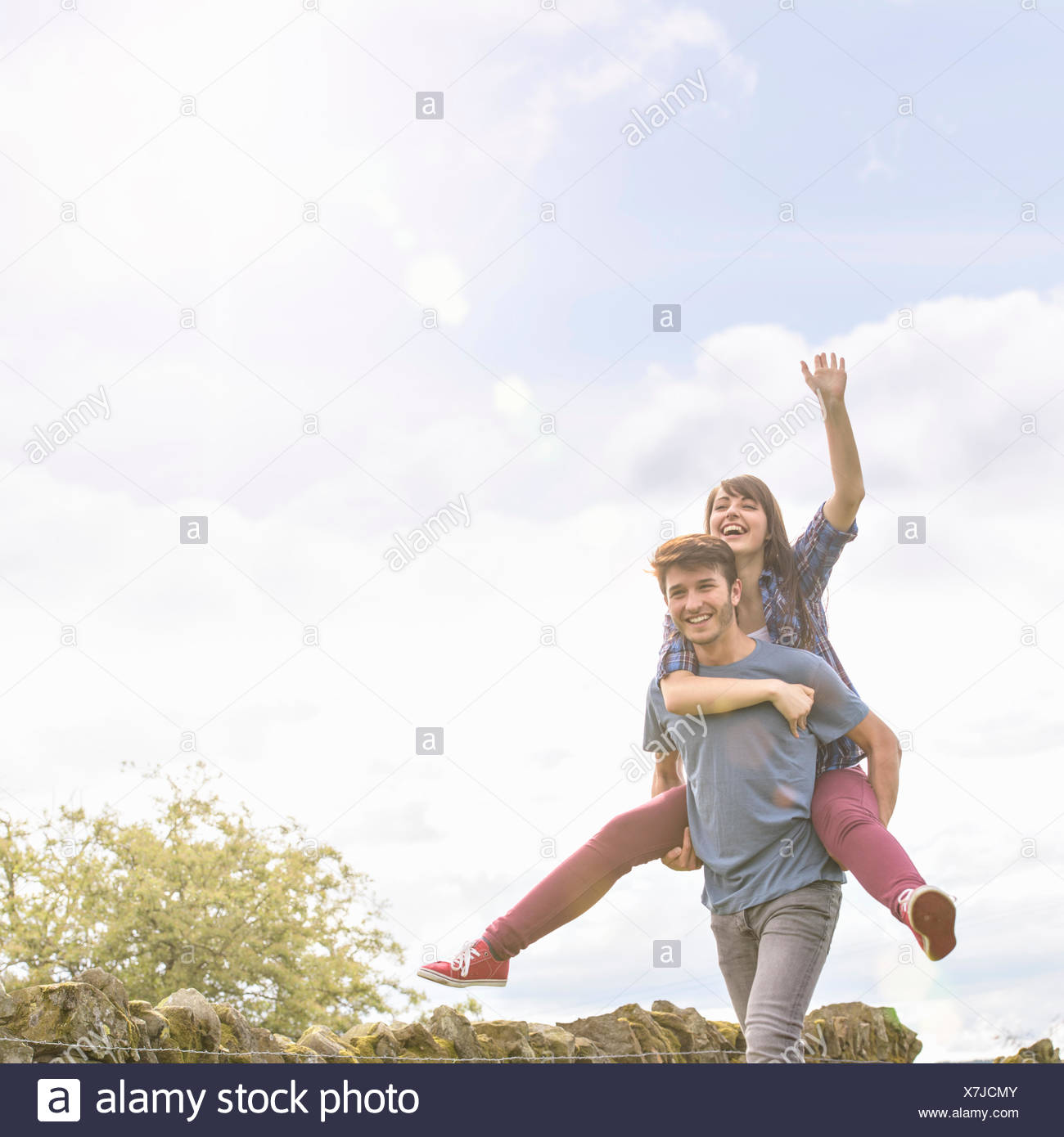 Young Man Giving Piggyback Ride To Girlfriend In